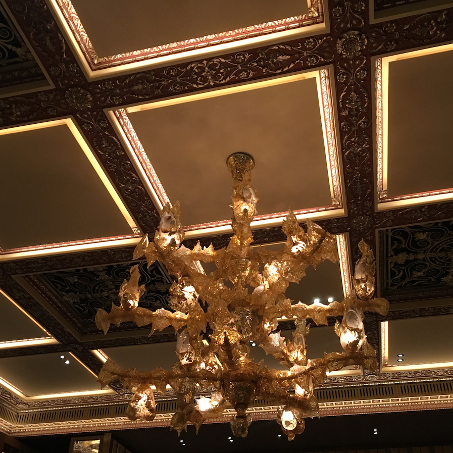 An ornate hand blown Murano glass chandelier hangs from the grade II listed gold ceiling in The Dorchester Grill Room