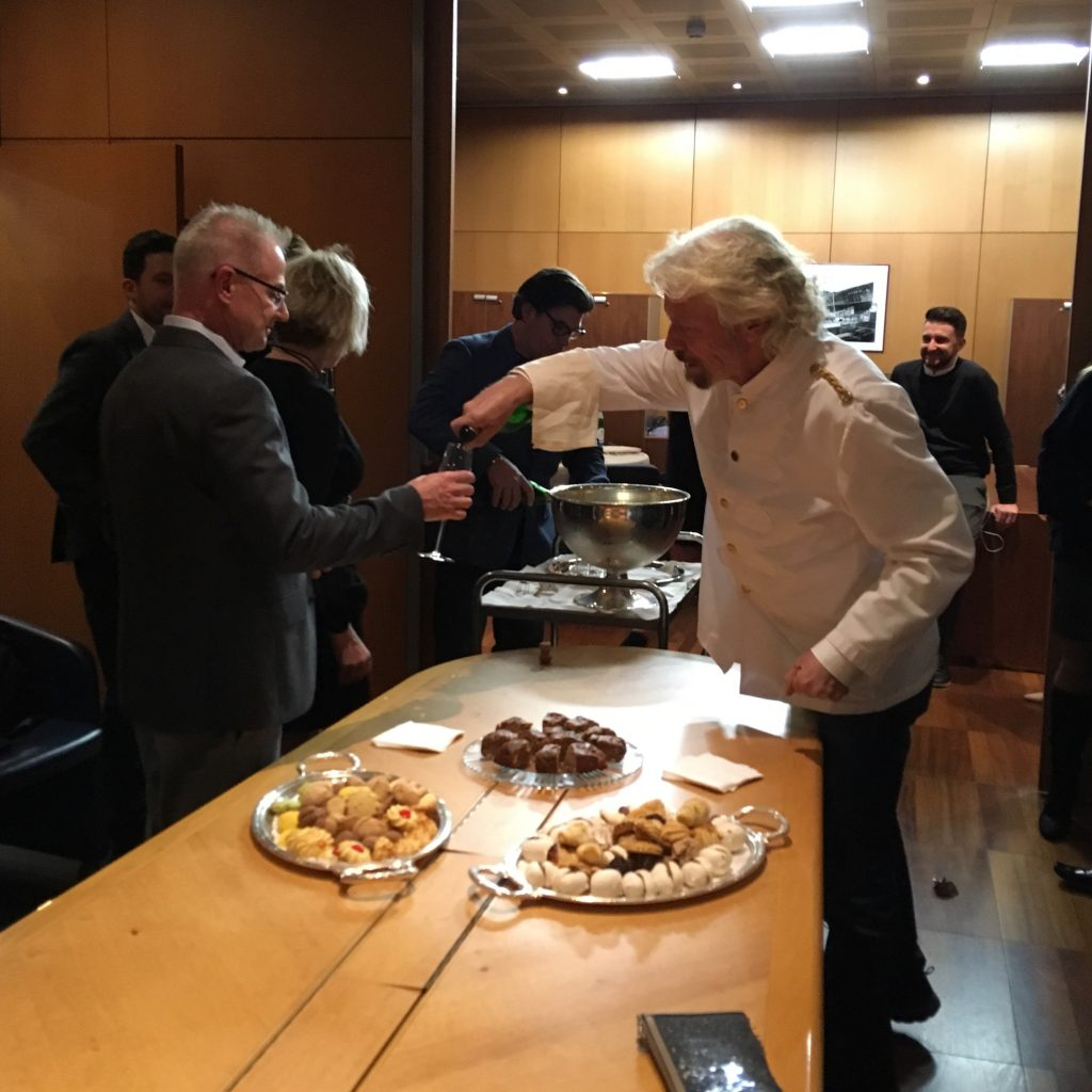Sir Richard Branson serving champagne to Travel Agents at the Fincantieri shipyard in Genoa