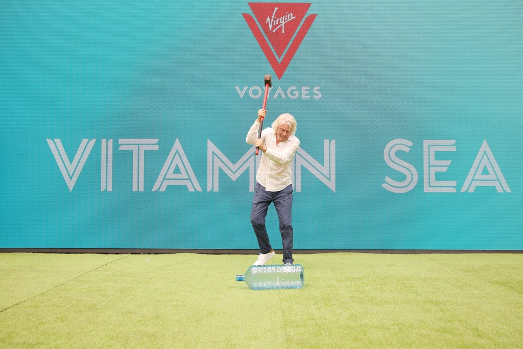 Sir Richard Branson takes a sledgehammer to a plastic bottle to demonstrate Virgin Voyages commitment to creating one of the cleanest fleets at sea.