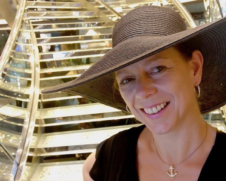 Flavia Gray cruise blogger of Ships and Champagne standing by the Swarovski Staircase onboard MSC Bellissima