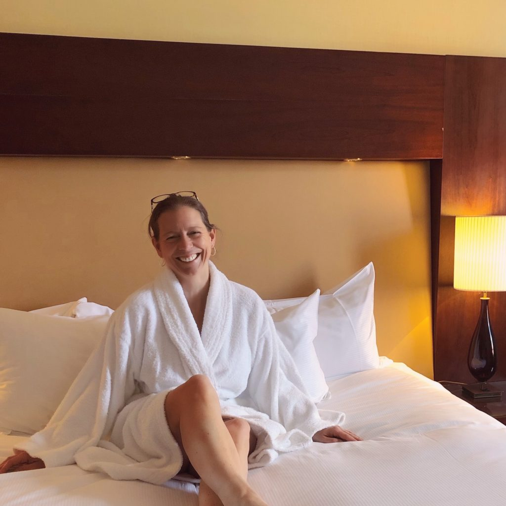 Flavia Gray laughing as she poses for a photograph on the bed wearing a bathrobe at the Hilton Hotel Nottingham