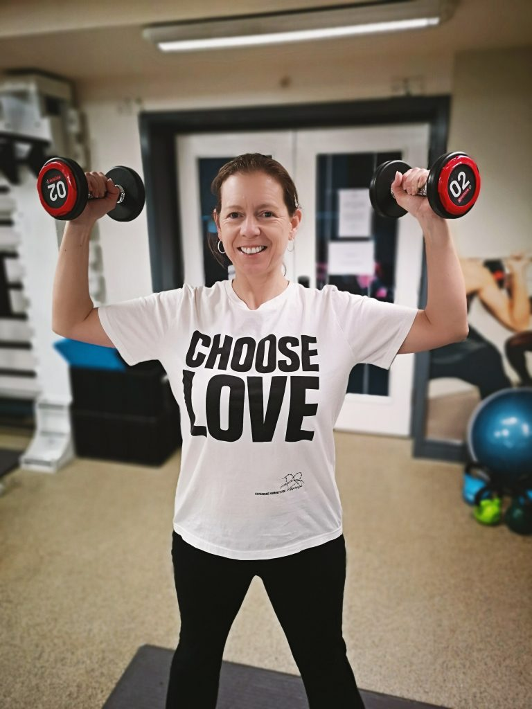 Flavia Gray lifting weights wearing a Choose Love tee shirt in the gym at Hilton Hotel Nottingham