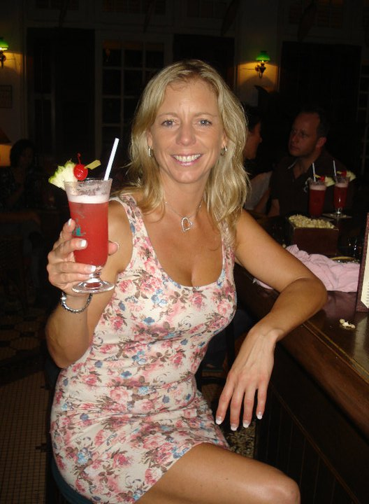 Flavia Gray holding a Singapore Sling in the Long Bar at Raffles Hotel, Singapore