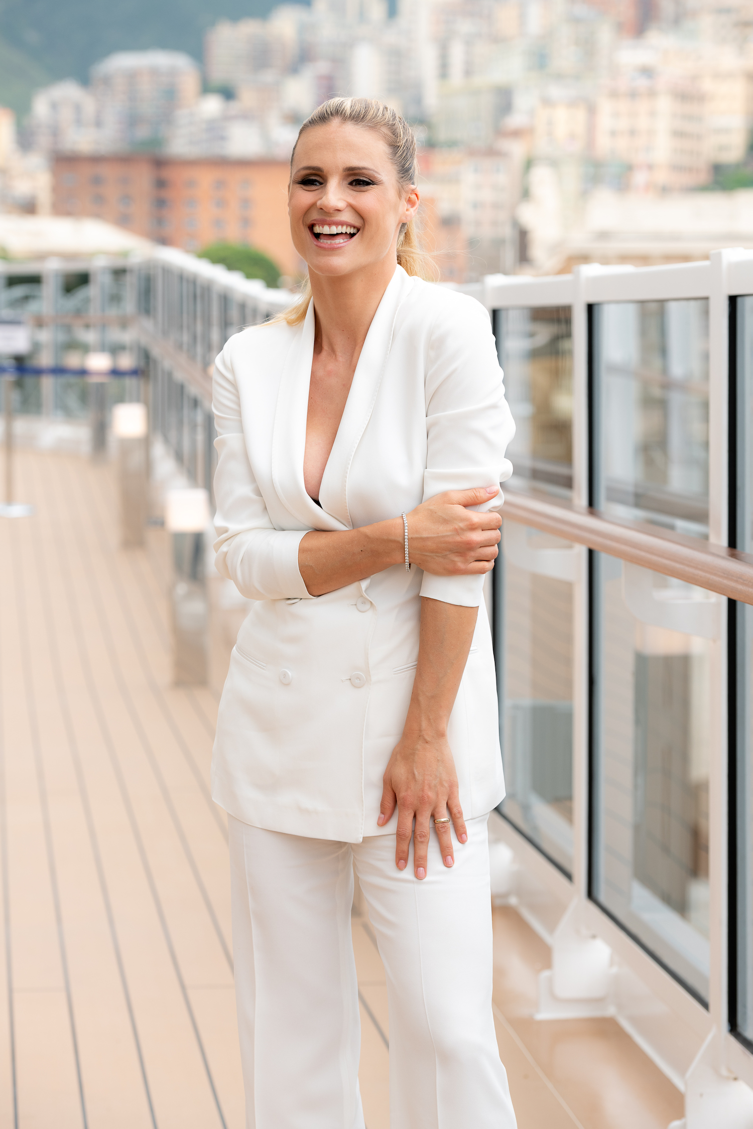 Michelle Hunziker standing on the deck of MSC Seaview docked in Genoa. Michelle is wearing a white trouser suite and has an open mouth smile.