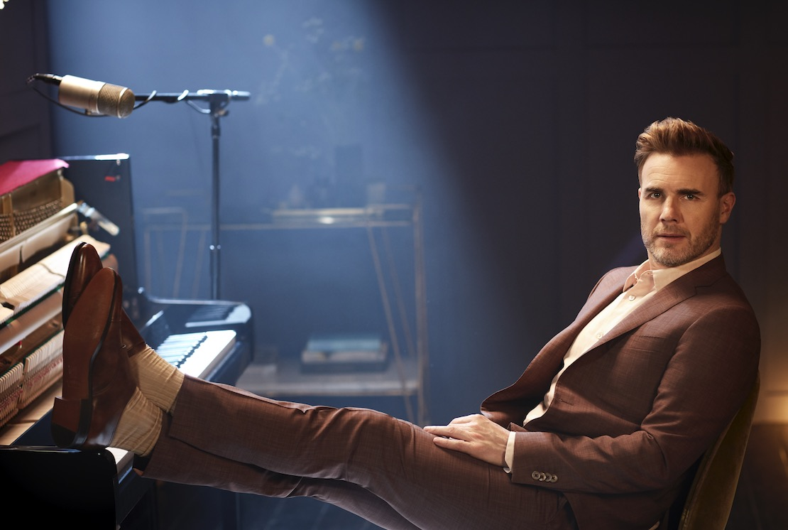 Gary Barlow with his feet on a piano